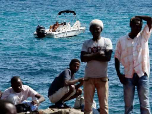 un-homme-profite-du-soleil-sur-son-bateau-alors-que-des-migrants-essentiellement-erythreens-et-ethiopiens-sont-bloques-a-la-frontiere-franco-italienne-entre-vintimille-et-menton-le-14-juin-2015_5358607