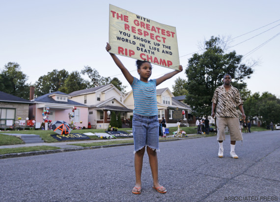 Akera Price-King, 9, carries a sign saluting Muhammad Ali on the street in front of Ali's boyhood home Friday, June 10, 2016, in Louisville, Ky. Ali's funeral procession is scheduled to pass by the house later in the day. (AP Photo/Mark Humphrey)