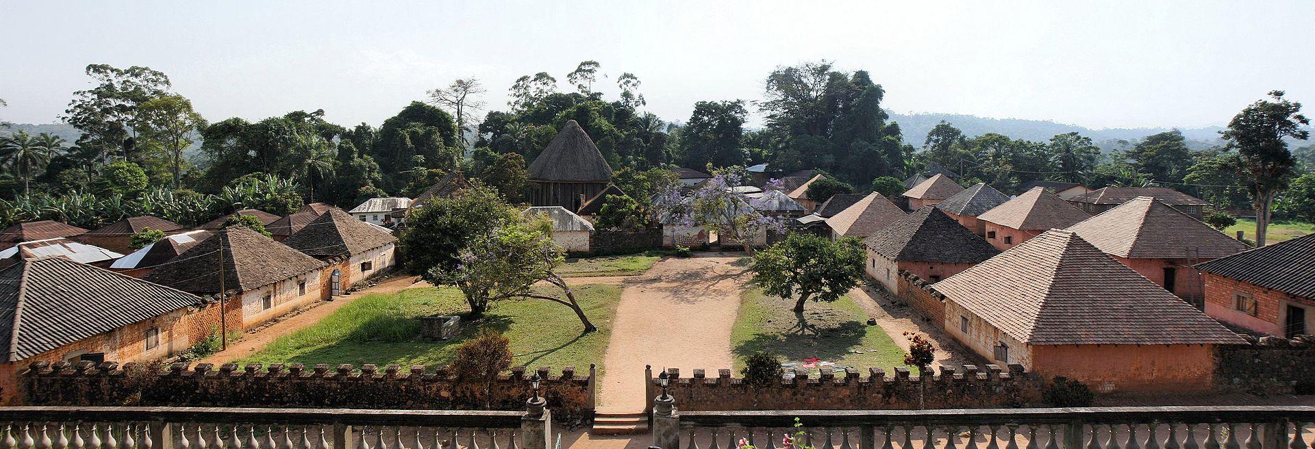 Chefferie de Bafut au nord de Bamenda. La cour principale avec les maisons des femmes à droite, recouvertes de tuiles, la forêt sacrée au fond.